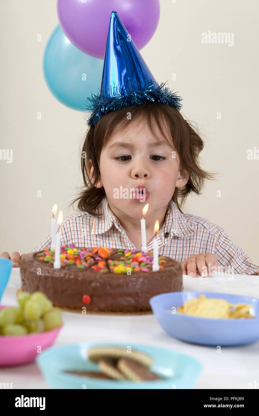 Boy Wearing Party Hat Blowing Out Candles On Birthday Cake Close Up