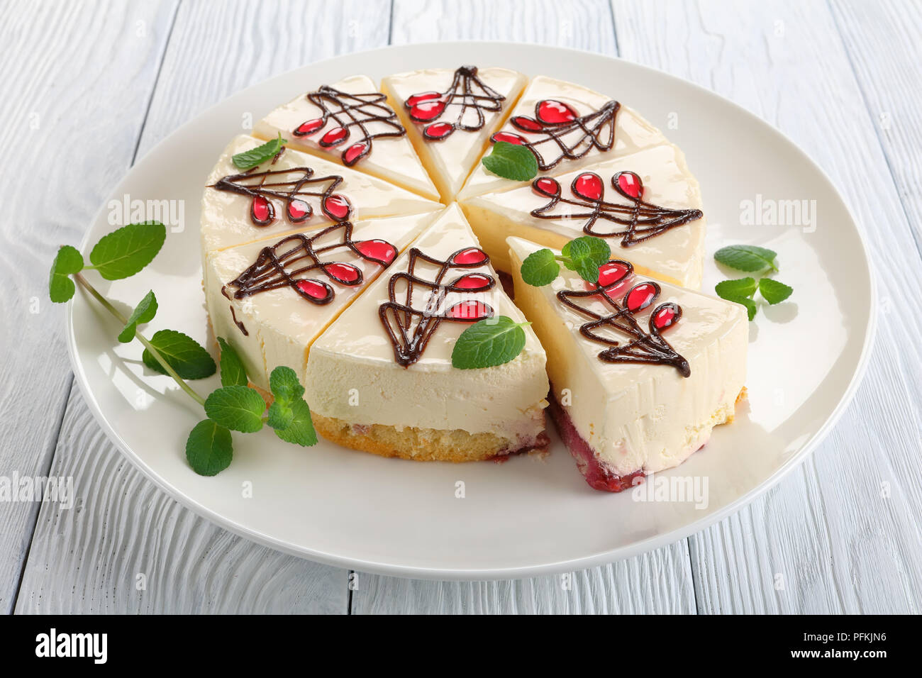 close-up of delicious ornately decorated with chocolate and jelly cheesecake with bottom layer consists of sponge cake with berry sauce, on white plat - Stock Image