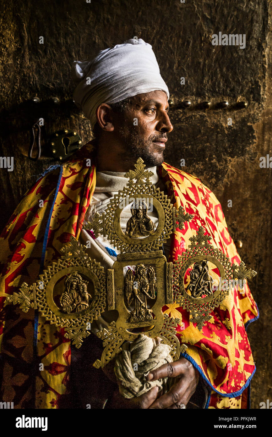 A priest stands in the doorway of Yemrehana Krestos Church, a church built in a cave 15 mile from Lalibela, Ethiopia, Africa - Stock Image