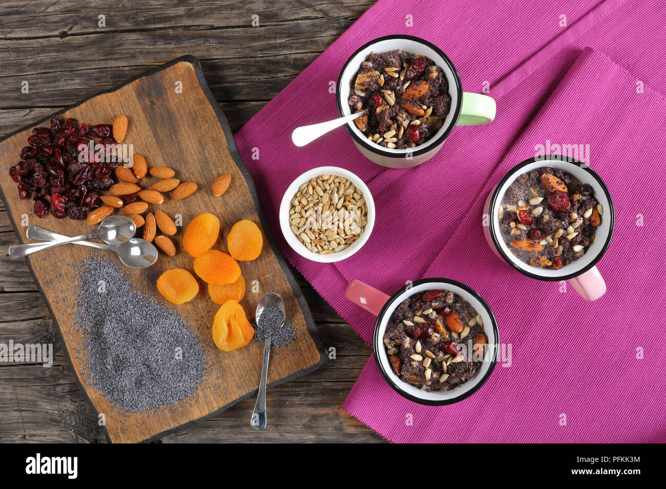 delicious christmas dessert or kutya of poppy seeds mixed with cooked whole wheat, dried fruits and nuts served in cups. ingredients on cutting board, - Stock Image
