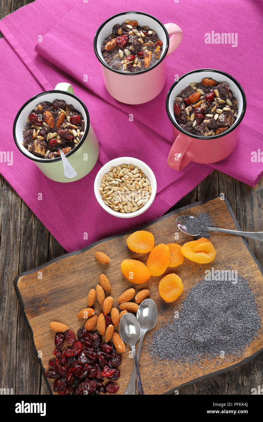 delicious christmas sweet dessert or kutya of poppy seeds mixed with cooked whole wheat, dried fruits and nuts served in cups. ingredients on cutting  - Stock Image