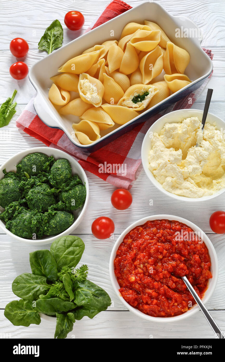 big pasta shells in the making to be stuffed with cheese and spinach. sauce marinara, fresh spinach leaves, soft cheese mixed with grated mozzarella i - Stock Image