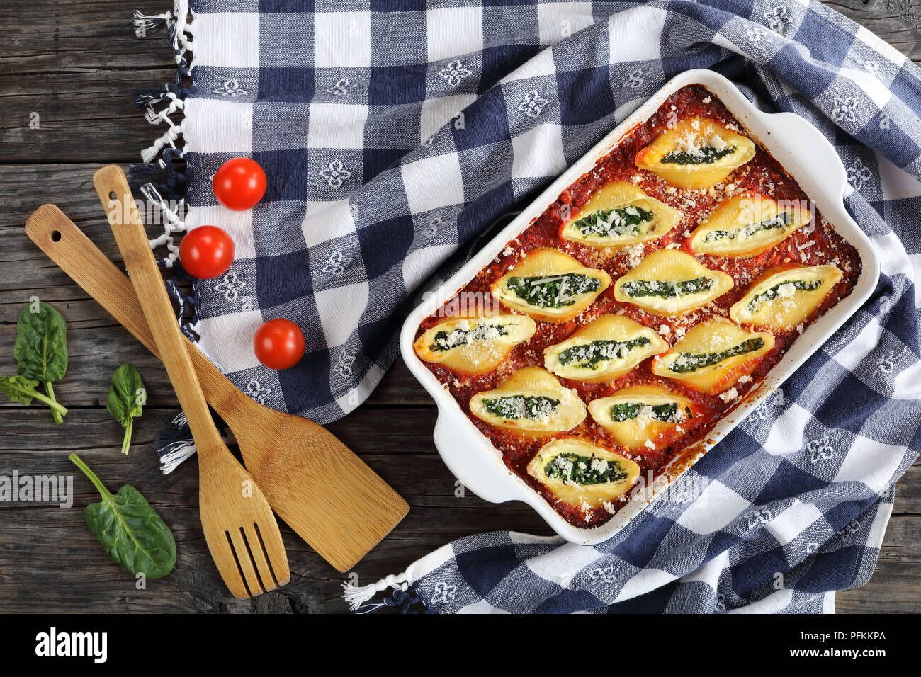 shell shape pasta stuffed with creamy soft cheese and spinach sprinkled with parmesan cheese in baking dish with kitchen towel and wooden spatulas on  Stock Photo