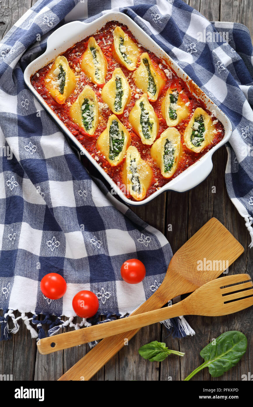 baked in oven shell shape pasta stuffed with creamy soft cheese and spinach sprinkled with parmesan cheese in baking dish with kitchen towel and woode Stock Photo