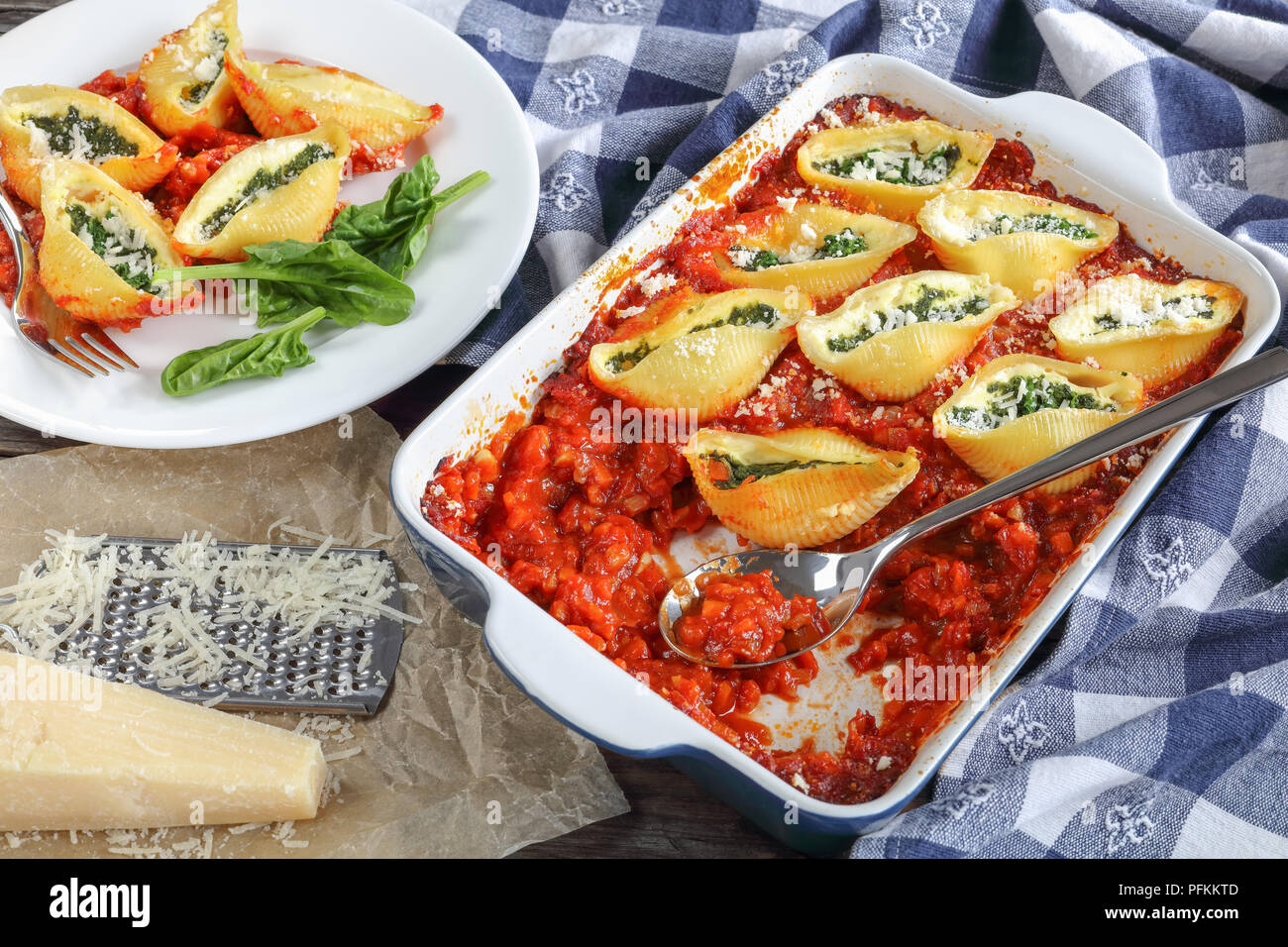 portion of shell shaped pasta stuffed with creamy soft cheese and spinach, baked in marinara sauce served on plate on dark wooden table with grated pa - Stock Image