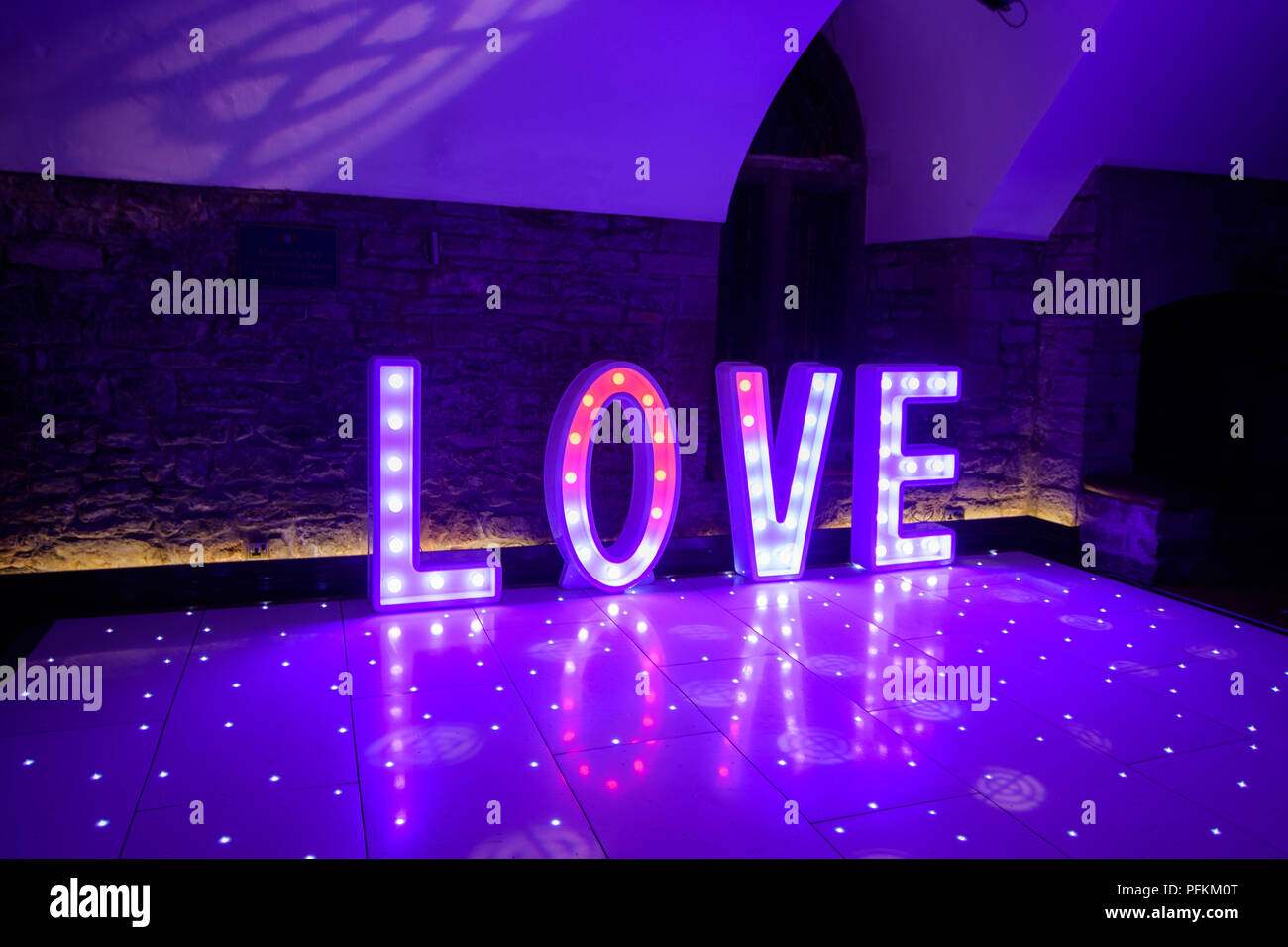 Illuminated Love sign in large letters at a wedding reception ready for the First Dance - Stock Image
