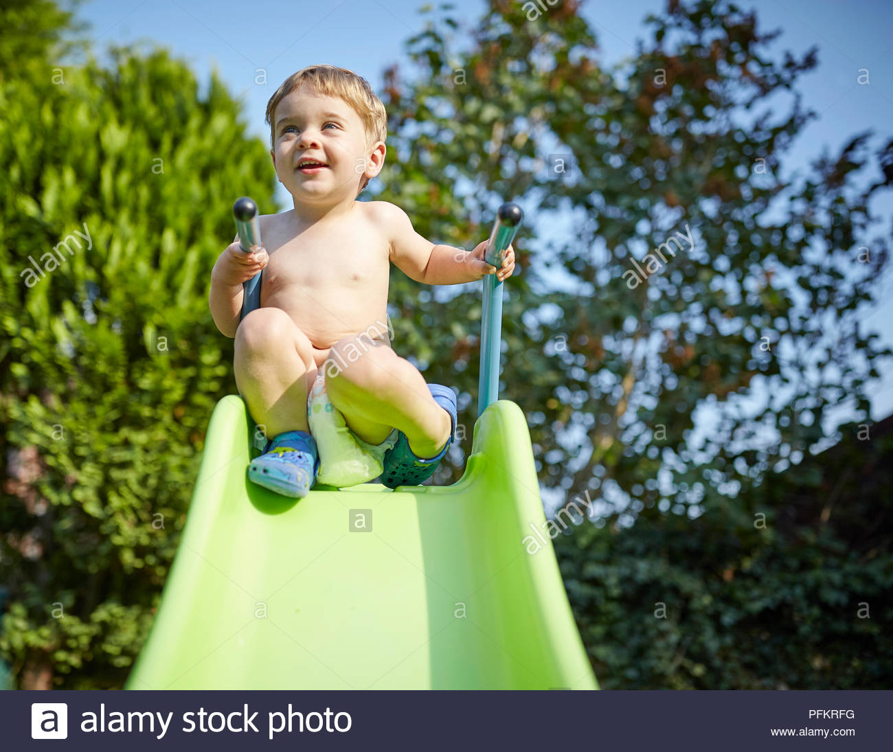 Toddler at the top of a slide outside - Stock Image
