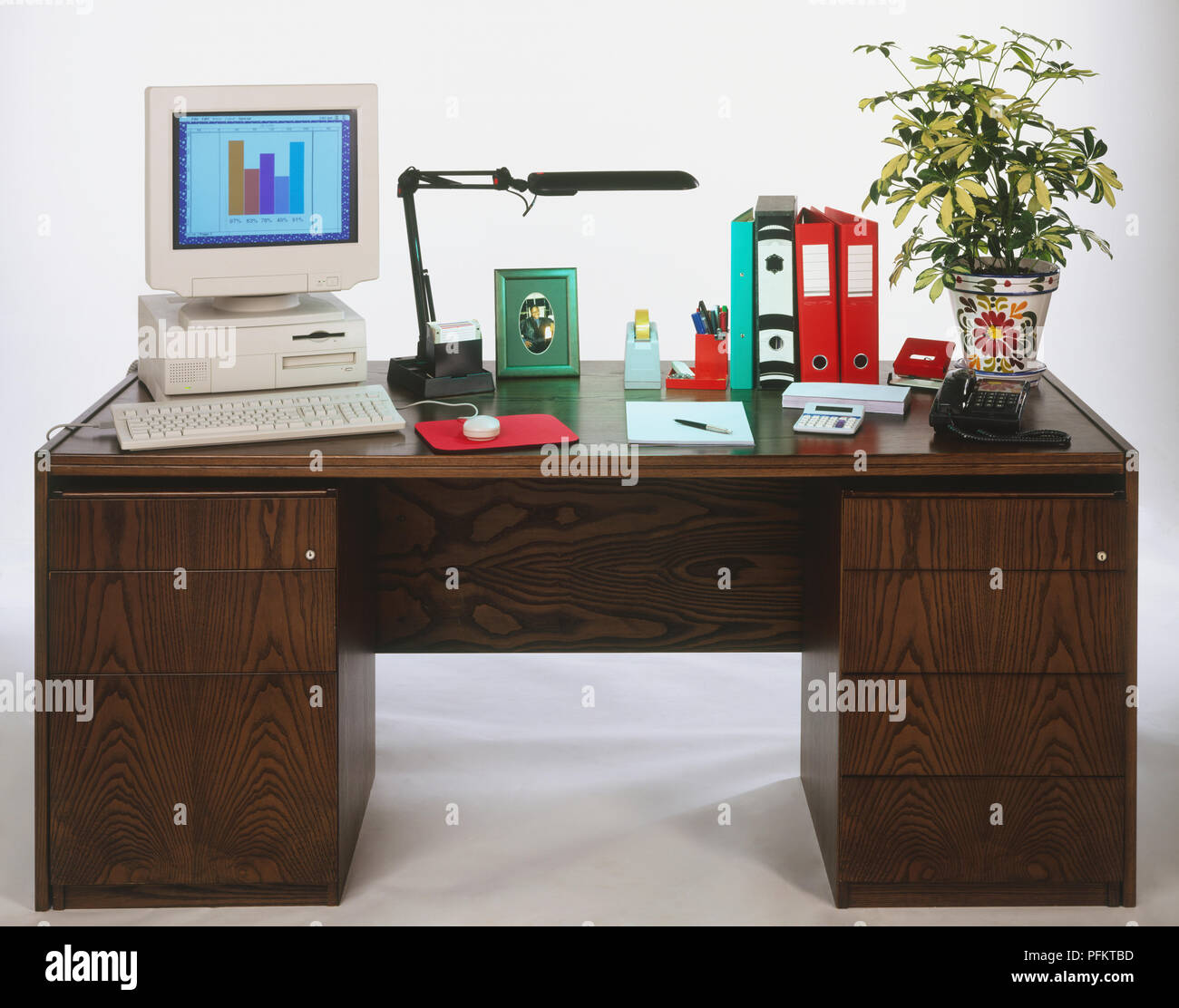 Desk top computer, desk lamp, framed picture, pocket calculator, telephone, various stationery and a houseplant on a wooden desk - Stock Image