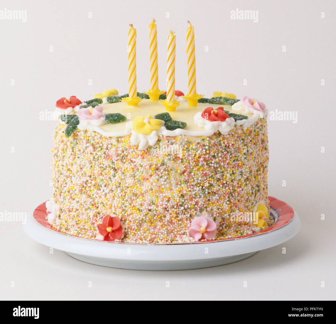 Birthday Cake Decorated With Candy Flowers Four Candles And A Border Of Multi Coloured Sprinkles