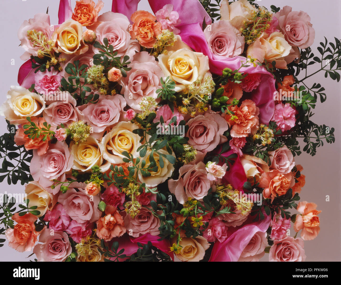 Overhead display of roses packed closely together varying in shades of pink with sprigs of green leaves. - Stock Image