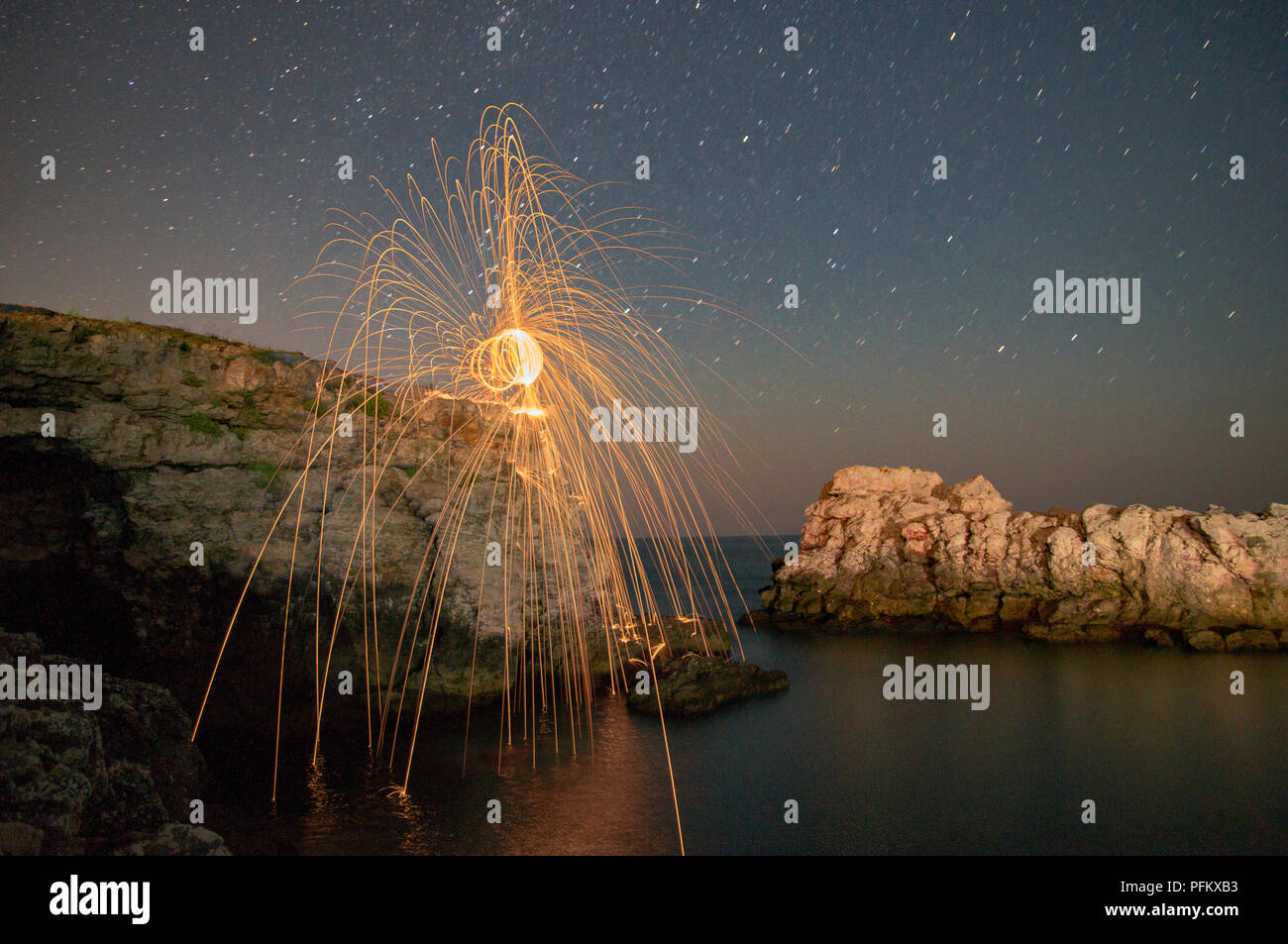 SPINNING STEEL WOOL FIREWORKS OVER THE ROCKS AND SEA Stock Photo