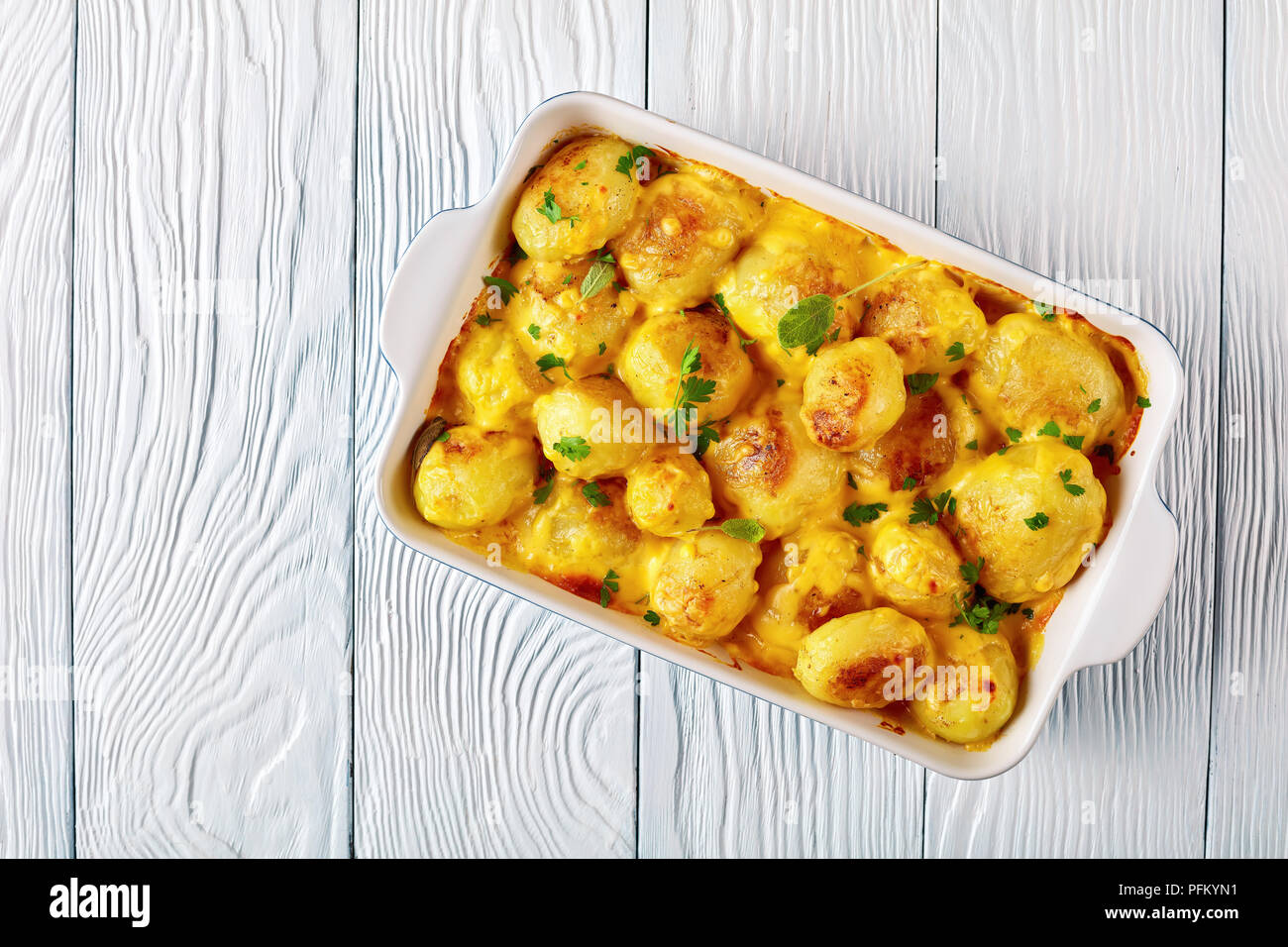 new potatoes with cheddar cheese butter sauce in a baking dish on a white wooden table, view from above, flat lay Stock Photo