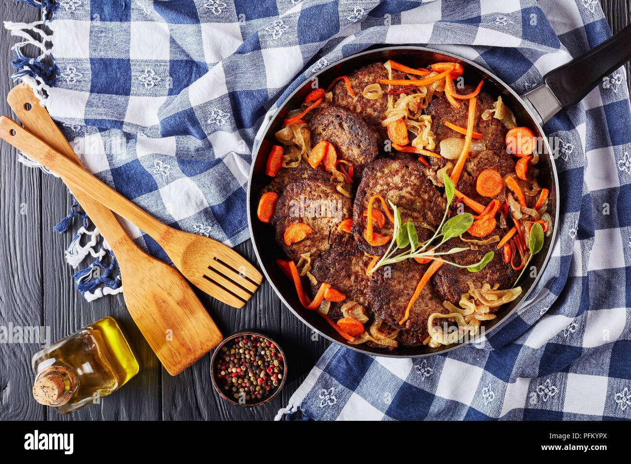 delicious Chicken liver pancakes with carrot, onion, herbs and spices in a skillet with kitchen towel and wooden spatulas on black table, view from ab - Stock Image