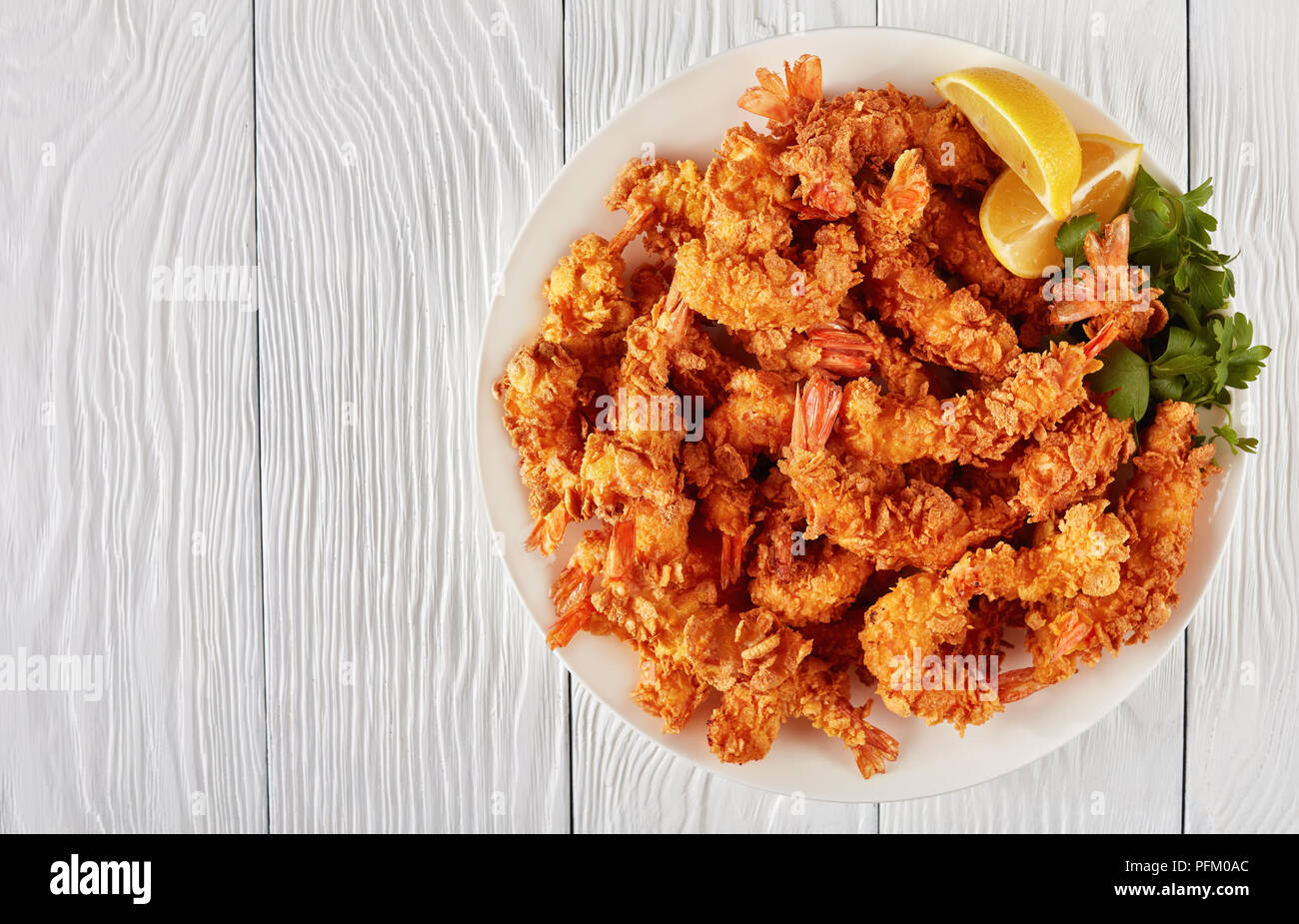 corn flakes breaded deep-fried shrimps on a white plate, view from above, flat lay - Stock Image