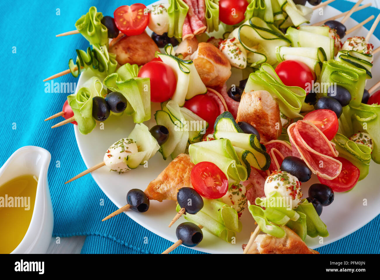 grilled chicken meat shish kebab skewers with zucchini ribbons, tomatoes, mozzarella balls, salami slices, black olives on a white plate, view from ab - Stock Image