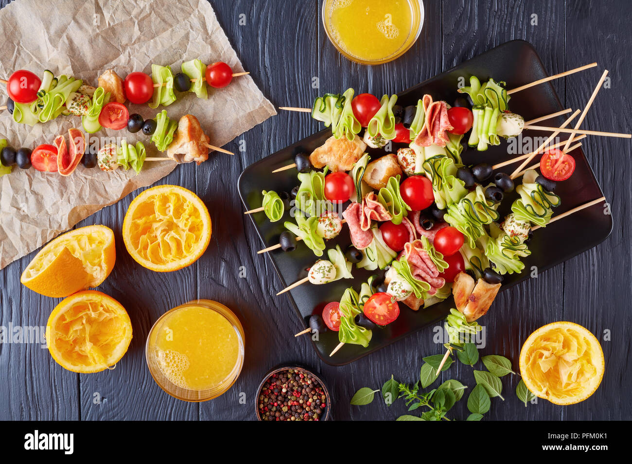 antipasto skewers with chicken meat, raw zucchini, cherry tomatoes,  mozzarella balls, salami slices, olives on a plate on a wooden table with orange  - Stock Image