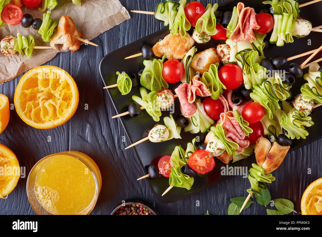 antipasto skewers with chicken meat, zucchini, cherry tomatoes,  mozzarella balls, salami slices, olives on a black plate on a wooden table with orang - Stock Image