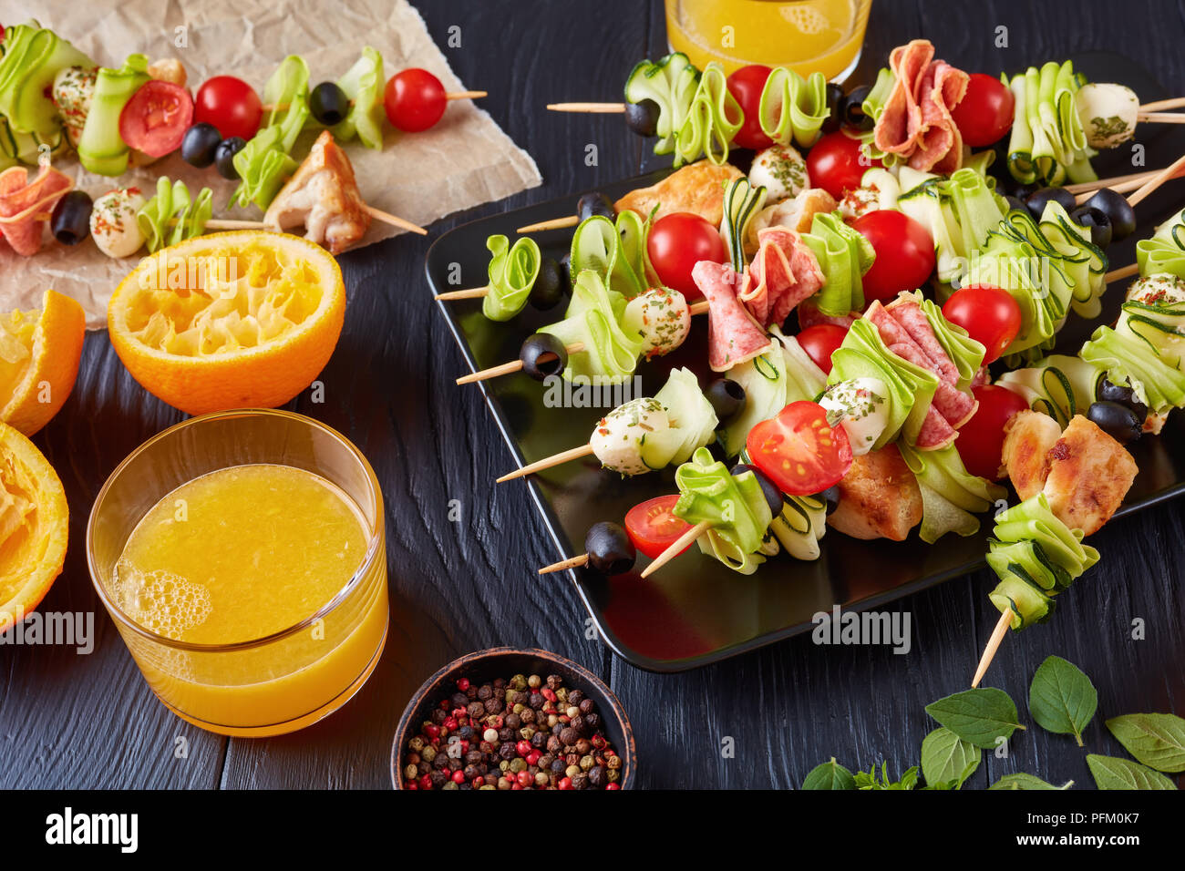 antipasto skewers with chicken meat, zucchini, tomatoes, mozzarella balls, salami slices, olives on a black plate on a wooden table with orange juice  - Stock Image