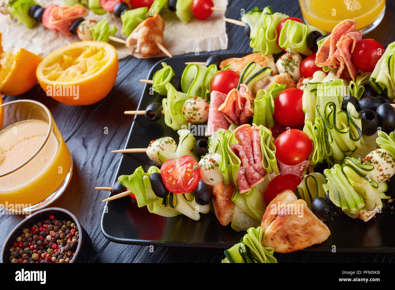 skewers with chicken meat, zucchini, tomatoes, mozzarella balls, salami slices, olives on a black plate on a wooden table with orange juice in glass c - Stock Image