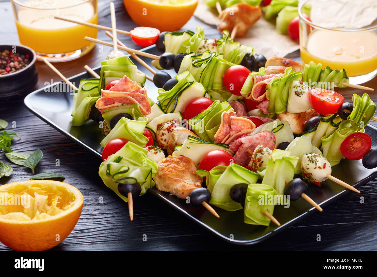 kebab on skewers with chicken meat, zucchini, tomatoes, mozzarella balls, salami slices, olives on a black plate on a wooden table with fresh orange j - Stock Image