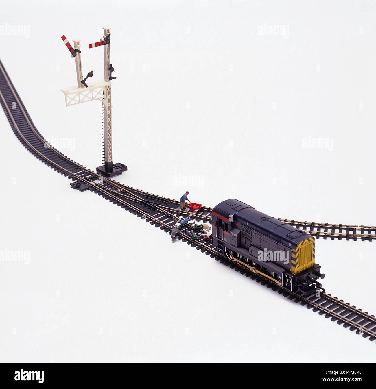 Miniature train with group of toy people lying on the tracks and a worker on another track nearby - Stock Image