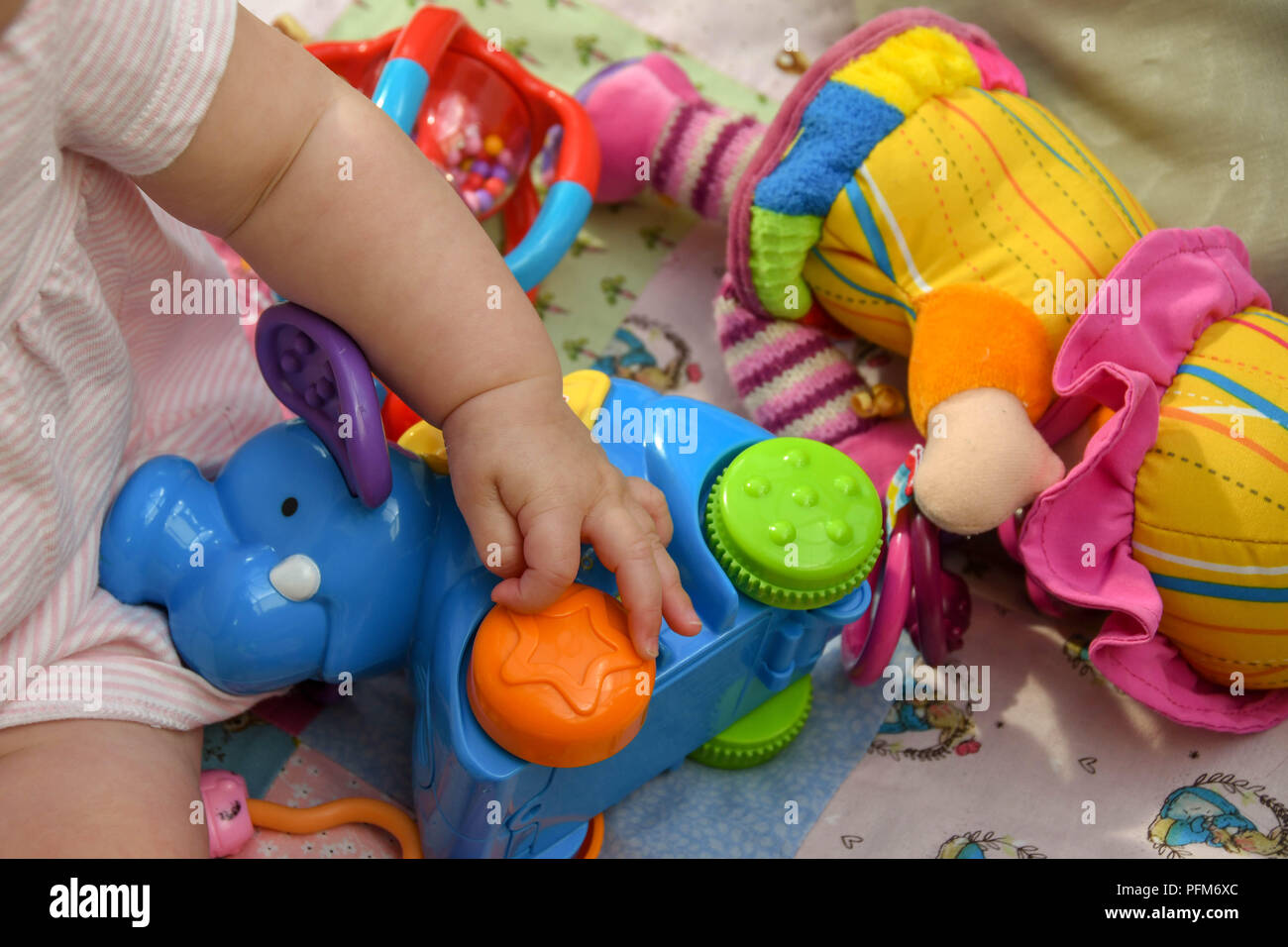 Close up of the hand of a baby playing with colourful plastic toy rings - Stock Image