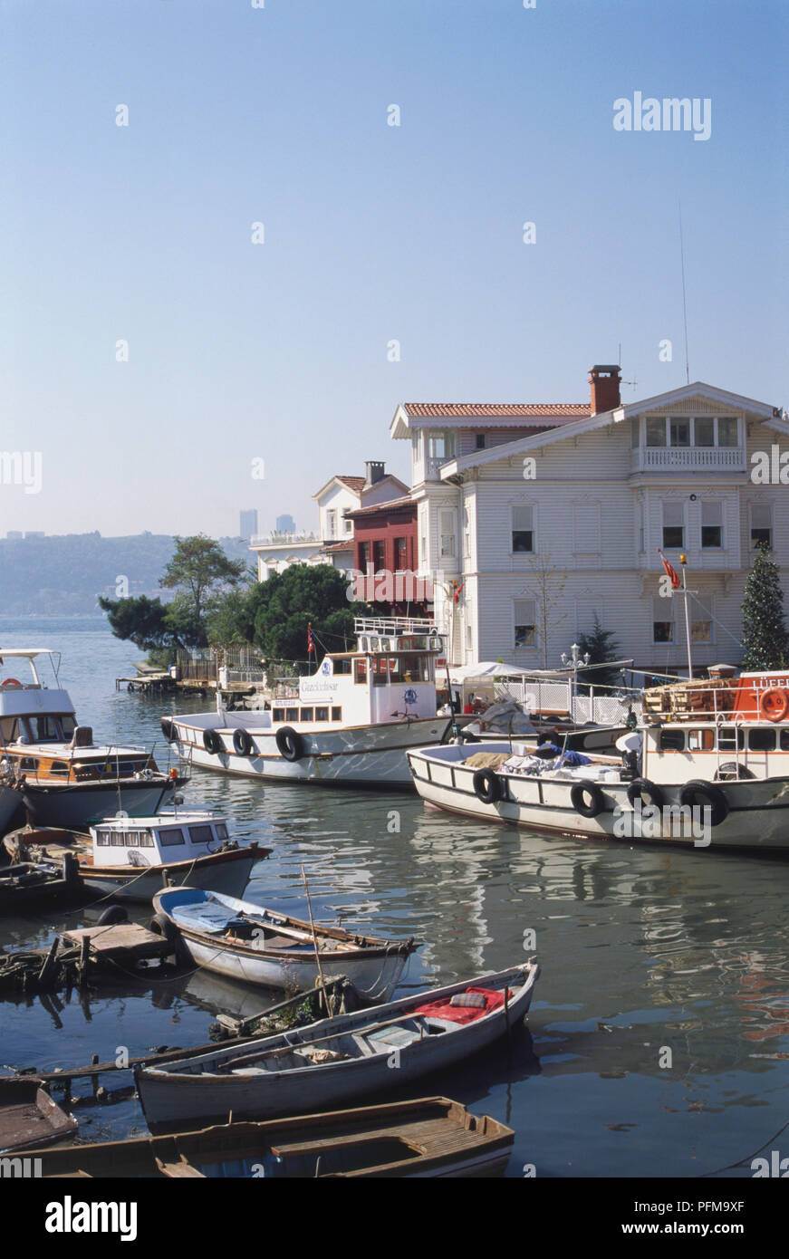 Asia, Turkey, Goksu River, various boats moored on the riverfront, cluster of buildings on waterfront, trees on edge, water and hilltop in background. - Stock Image