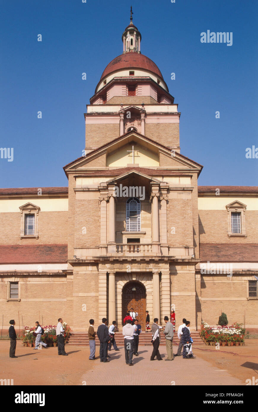 India, New Delhi, Neo-Classical Cathedral Church of the Redemption, designed by architect Henry Alexander Medd, red coloured, tall central dome, ornate wooden door, flower pots beside entrance, people standing. - Stock Image