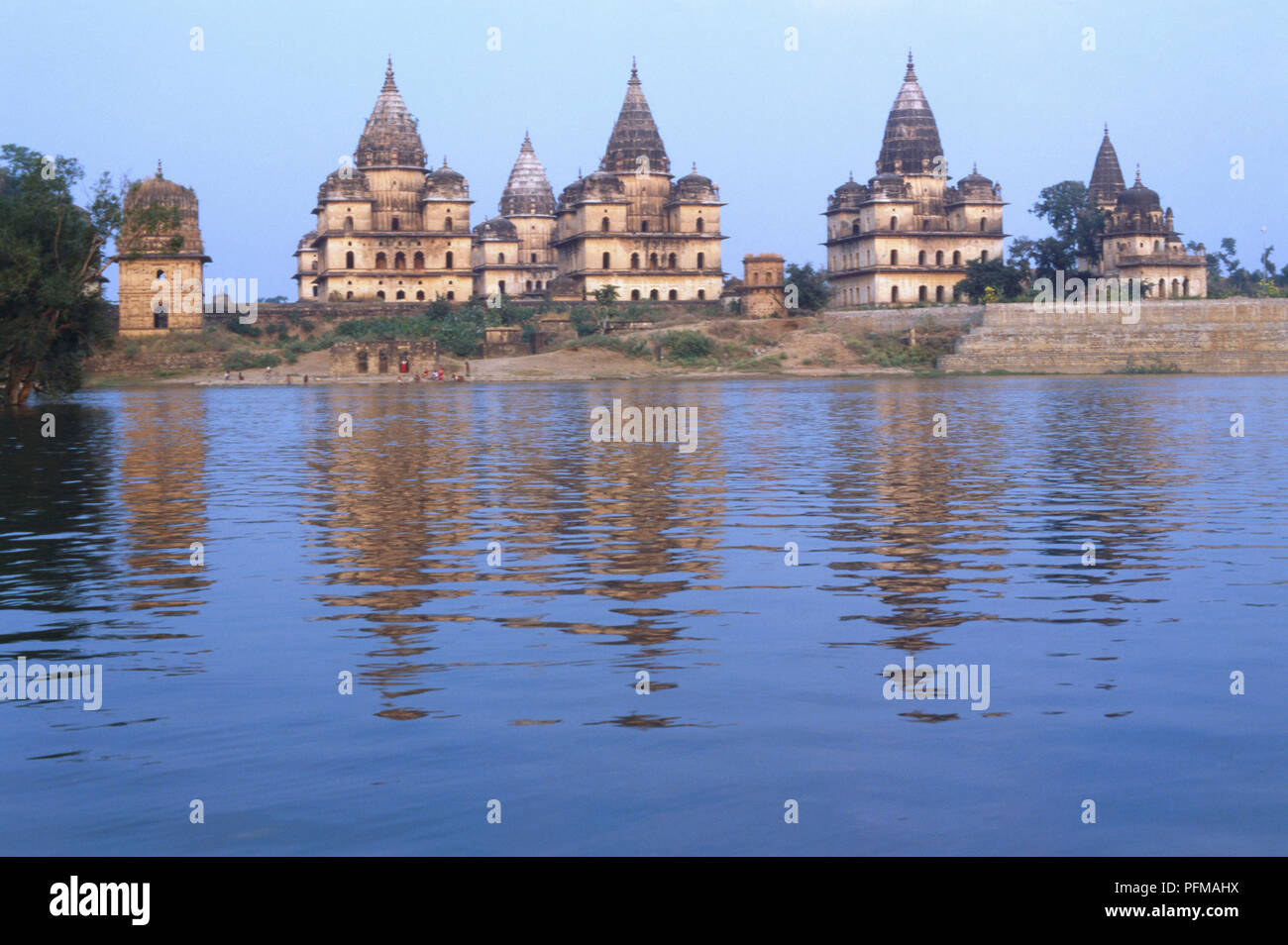 India, Orchha, the early capital of the Bundela kings, picturesquely situated on the banks of the Betwa, temples, are blend of fort and temple styles, soaring spires, red buildings becoming blackened at top, reflecting on river in foreground. - Stock Image