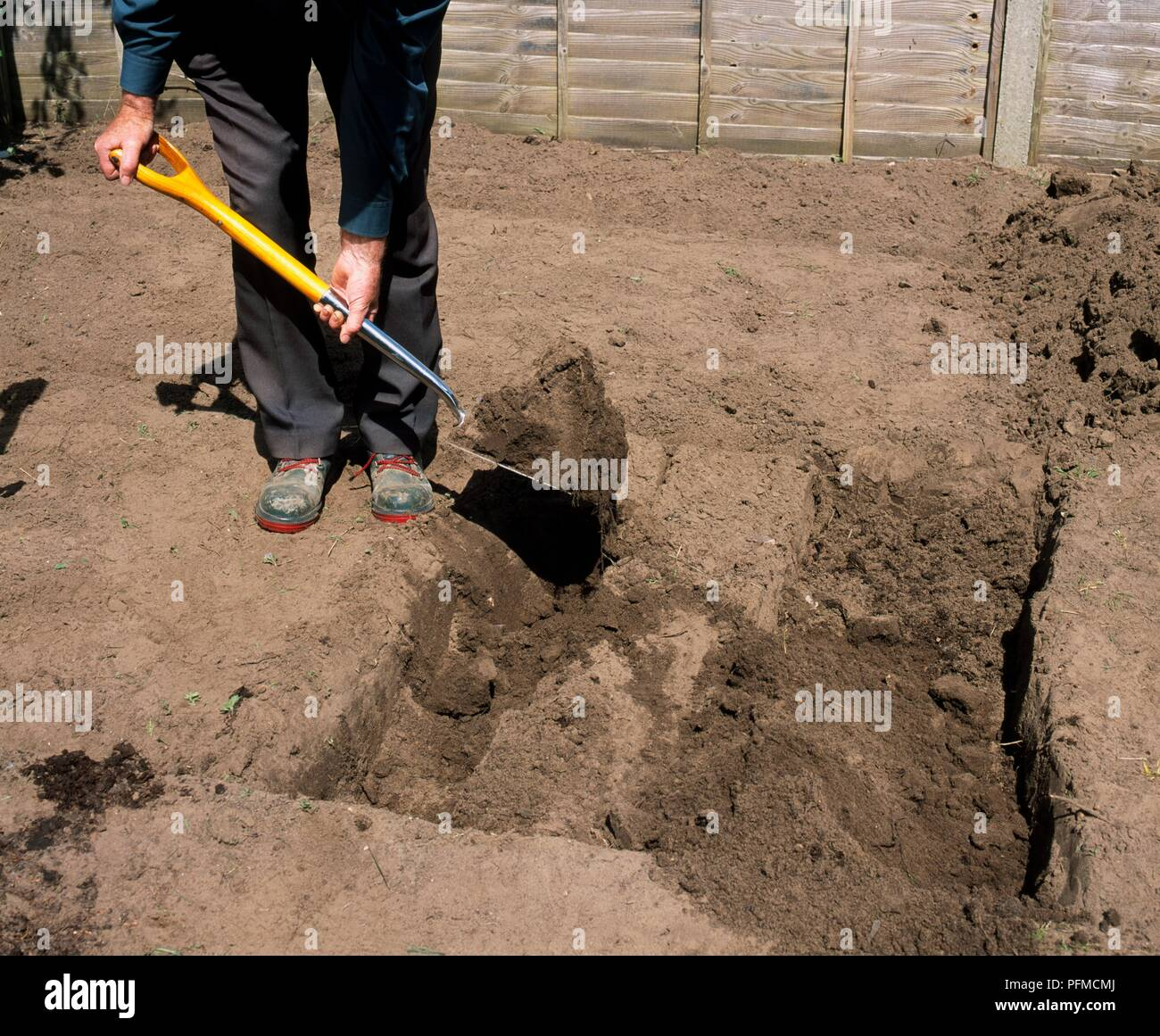 Man using spade to dig trench Stock Photo: 216193282 - Alamy