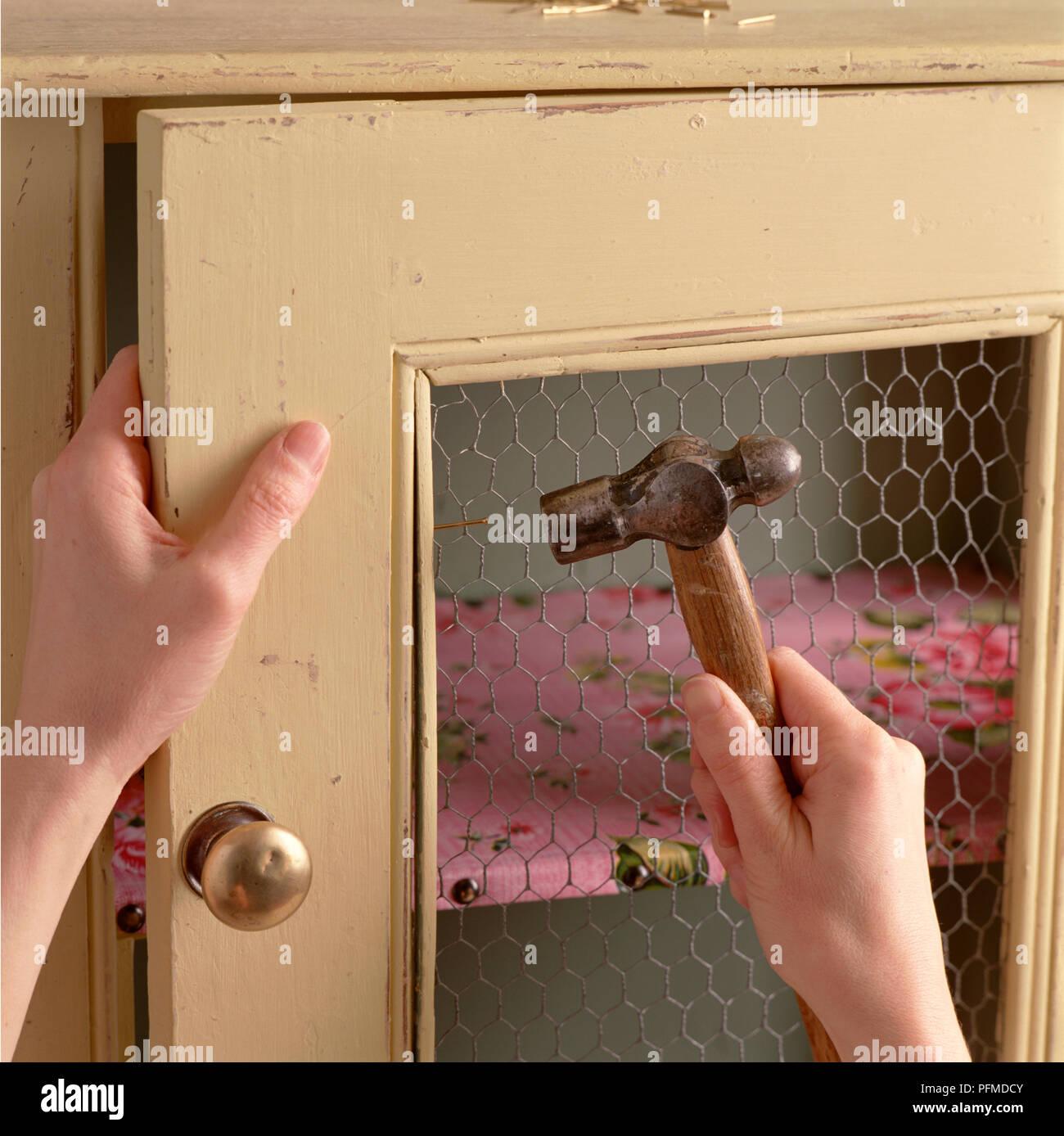 Hands hammering old cupboard, attaching chicken wire inside door of ...
