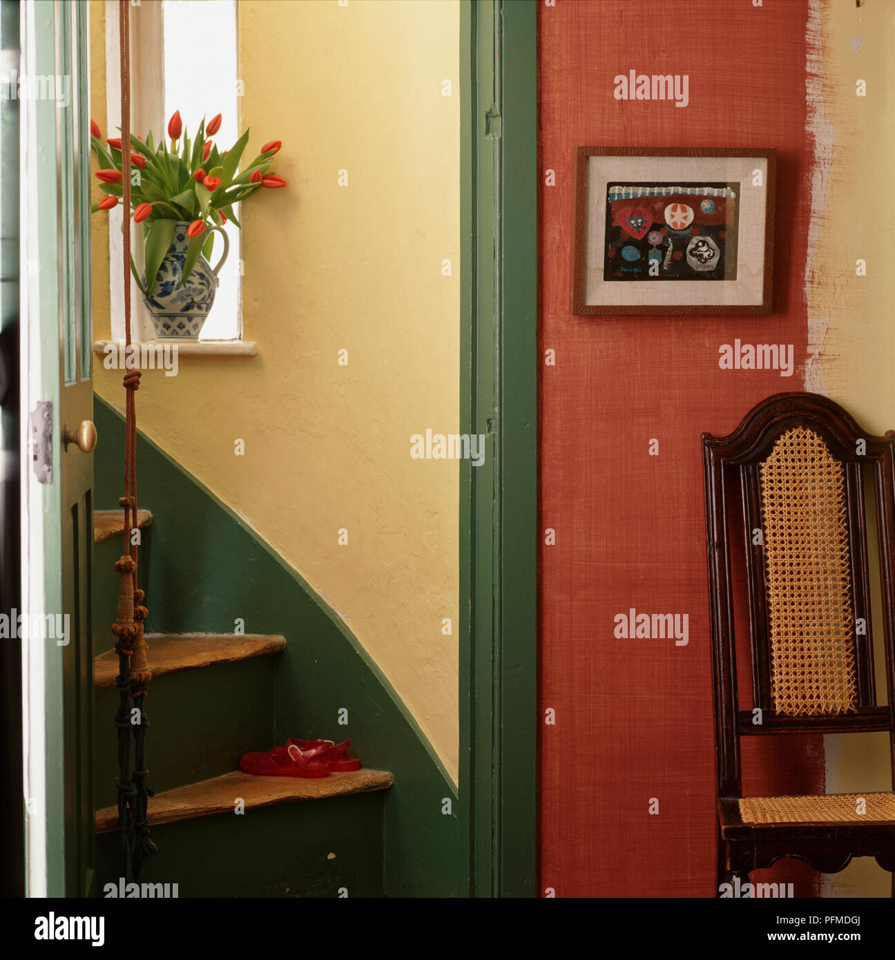 Red room with upright chair and framed picture, green doorframe leading to wooden spiral stairs with green painted skirting board, yellow walls, tulips standing in jug on sunny windowsill, red jelly shoes on step, bell rope hanging down. - Stock Image