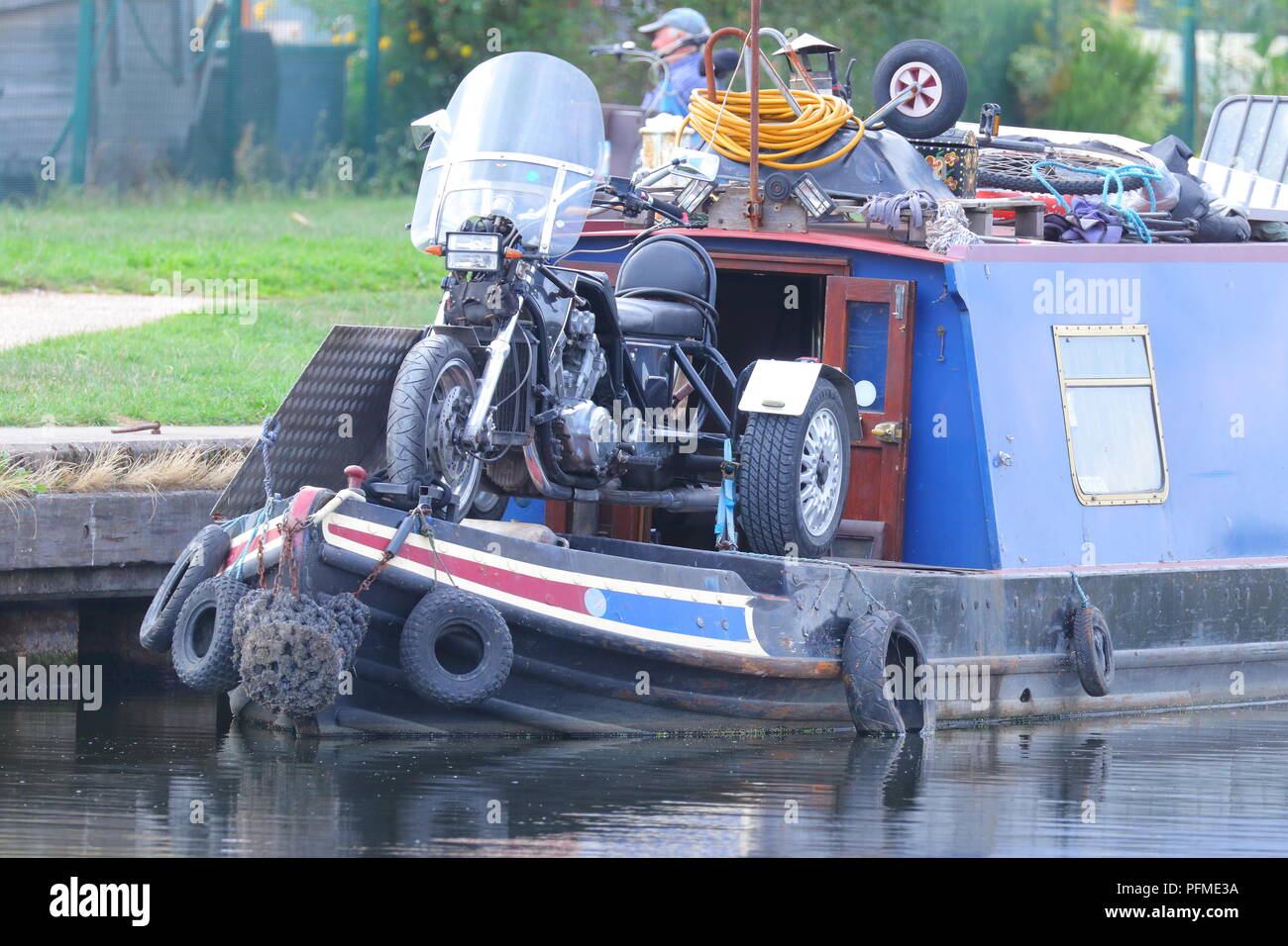 A Narrowboat with additional transport on board to be able to be more mobile. - Stock Image