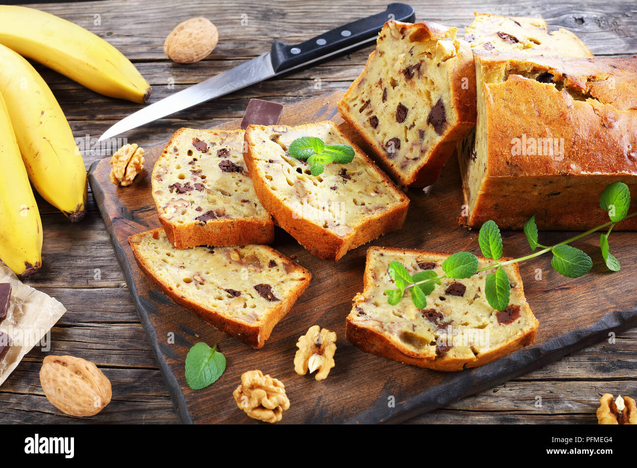 freshly baked delicious banana bread with walnuts and chocolate pieces cut in slices on cutting board. ingredients on rustic wooden table, american cu - Stock Image