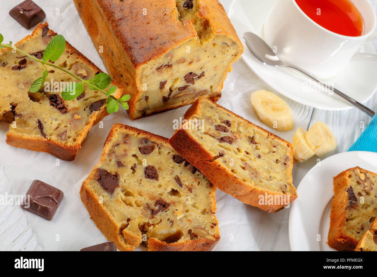 close-up of freshly baked delicious banana bread with walnuts and chocolate pieces cut in slices on cutting board. ingredients and cup of tea on woode Stock Photo