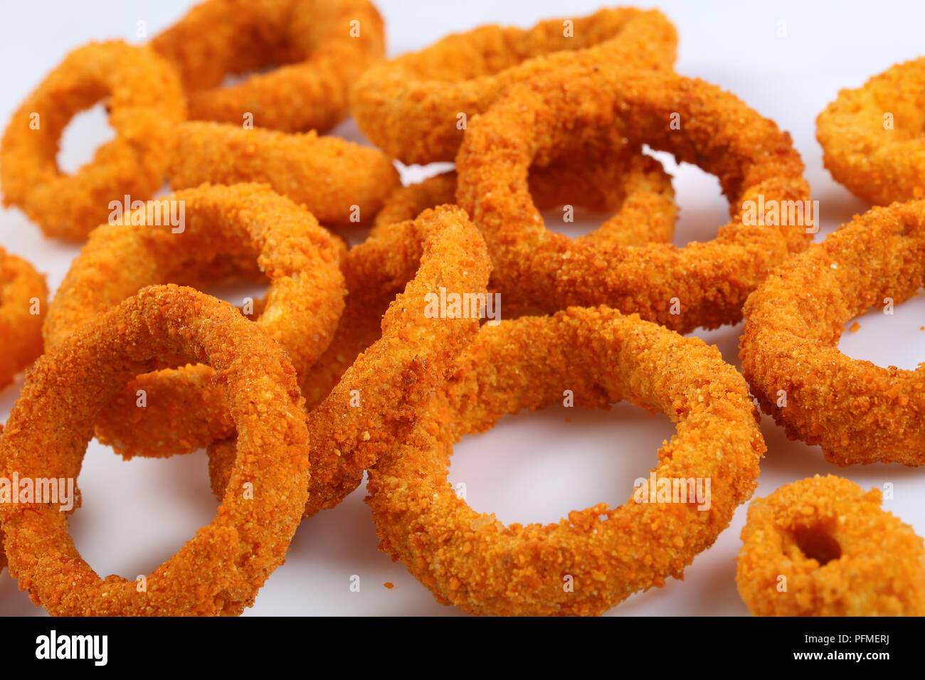 close-up of delicious golden breaded and deep fried crispy onion rings on white plate, view from above - Stock Image