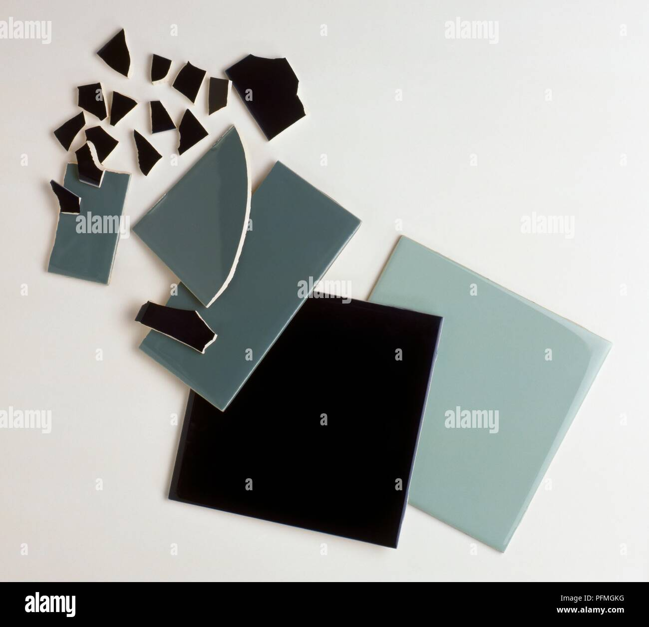 Black and grey tiles and tile fragments to be used in mosaic - Stock Image