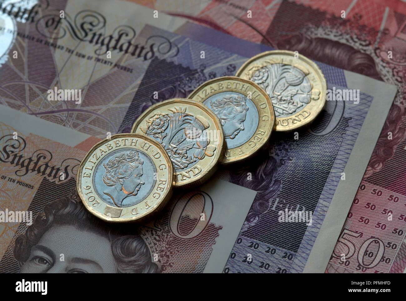 New British (GBP) pound coins resting on £50, £20 and £10 pound notes. - Stock Image