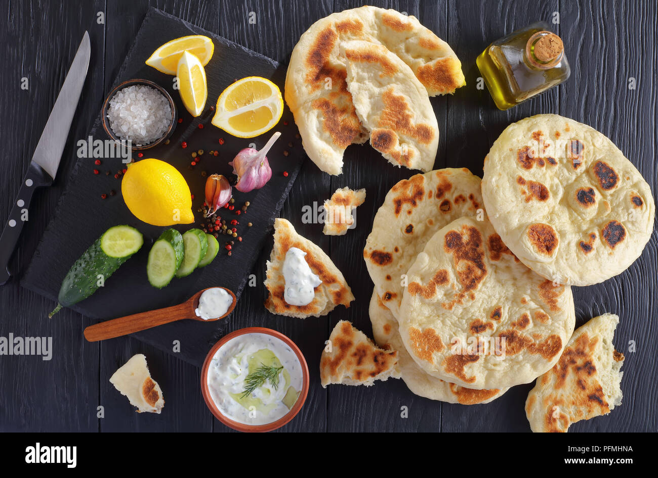 freshly baked pita bread on black wooden table with savory tzatziki sauce. ingredients on stone cutting board, horizontal view from above - Stock Image