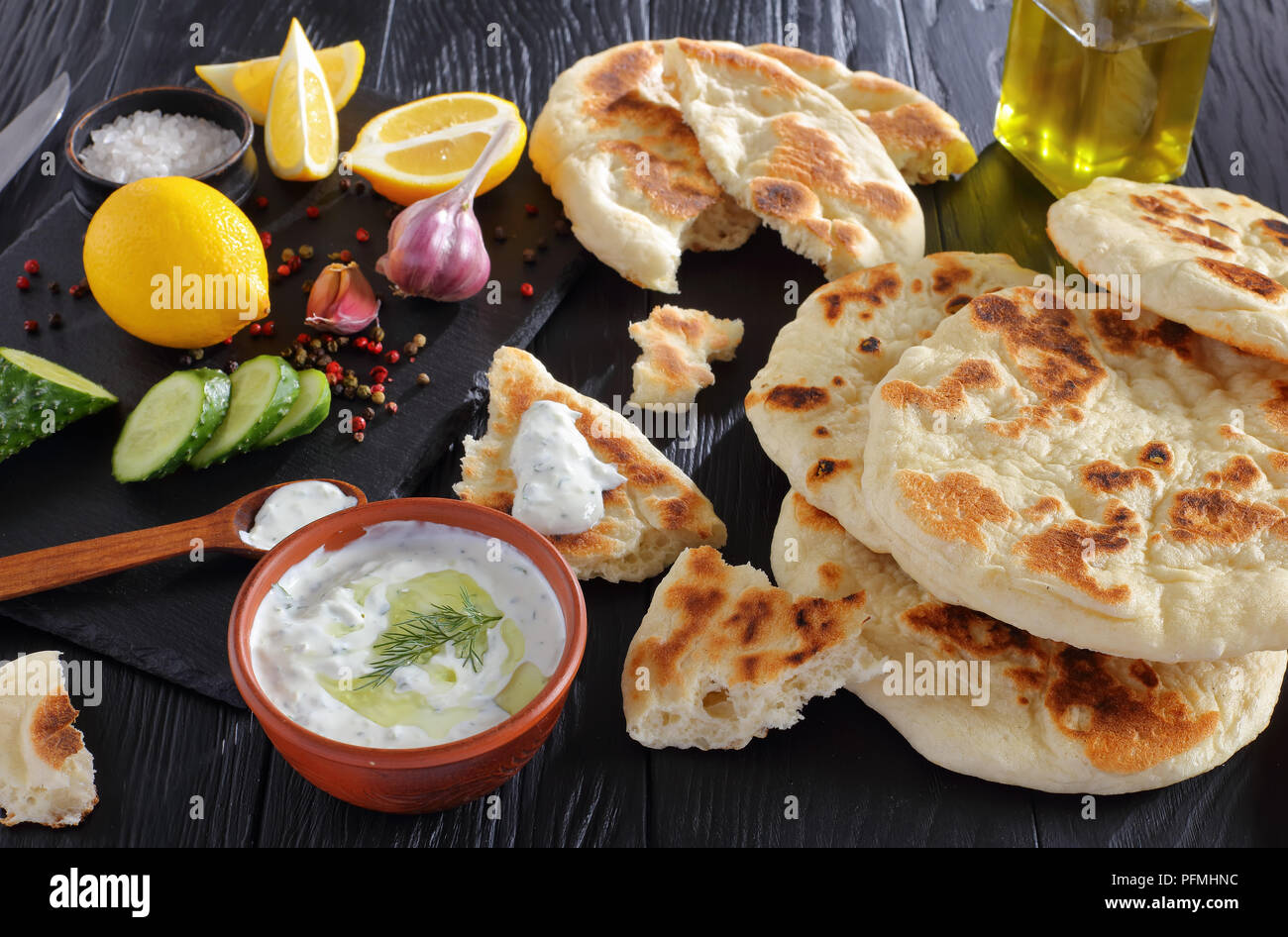 freshly baked pita bread on black wooden table with savory tzatziki sauce. ingredients on stone cutting board, horizontal view from above, close-up - Stock Image