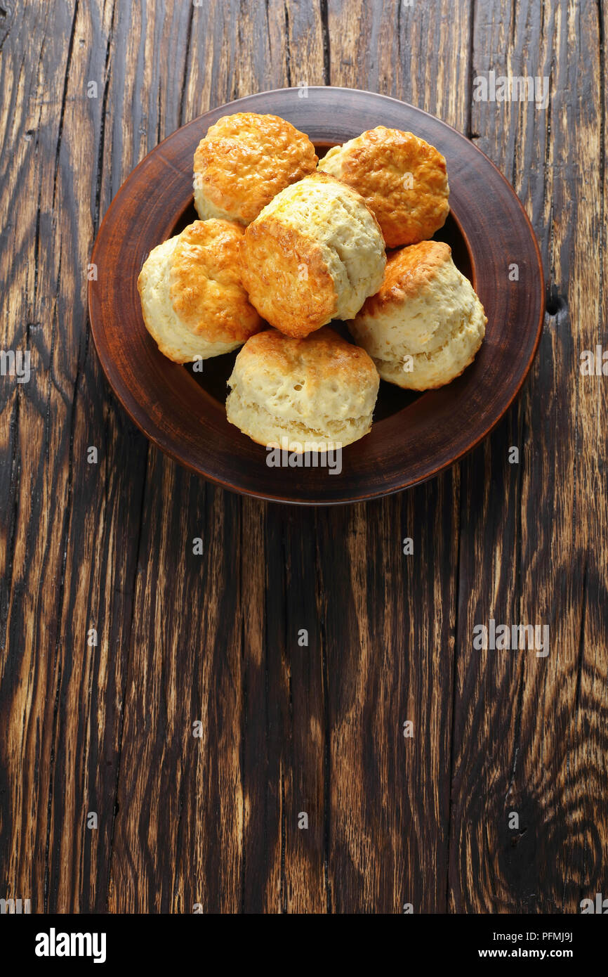delicious freshly baked homemade english scones on clay plate on wooden table,  vertical view from above - Stock Image
