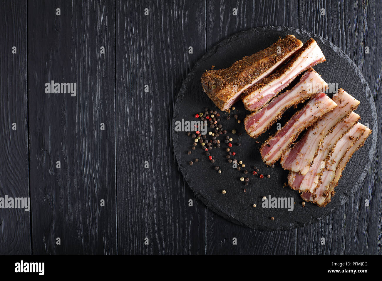delicious spiced smoked speck cut in slices on black slate plate, view from above Stock Photo