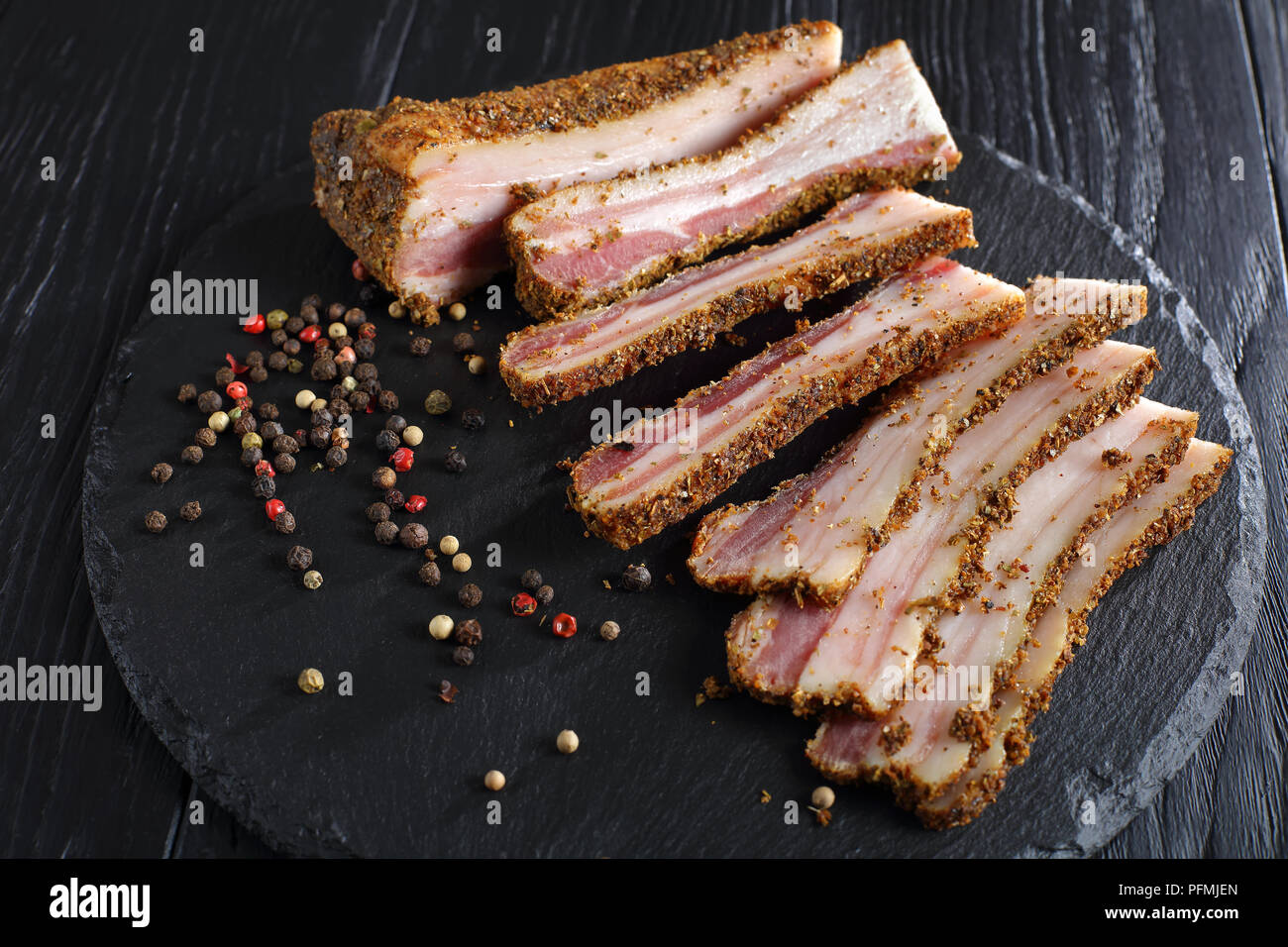 delicious spiced smoked speck cut in slices on black slate plate on wooden table, view from above, close-up Stock Photo