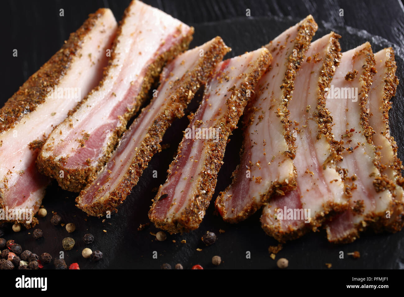 close-up of delicious spiced smoked speck cut in slices on black round stone plate on wooden table, horizontal view from above, macro Stock Photo