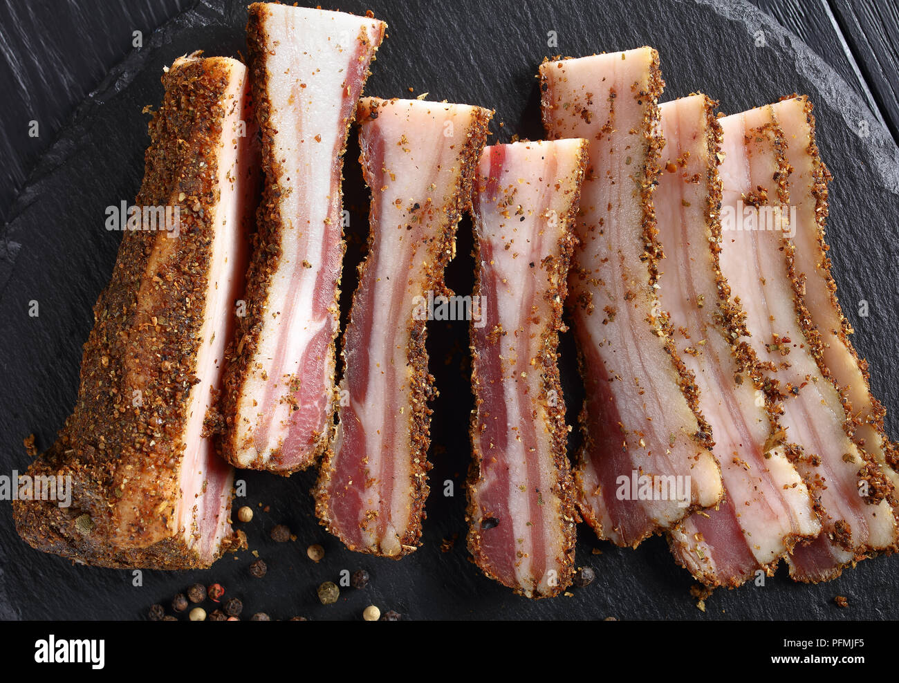 close-up of spicy smoked speck cut in slices on black round stone plate on wooden table, horizontal view from above Stock Photo