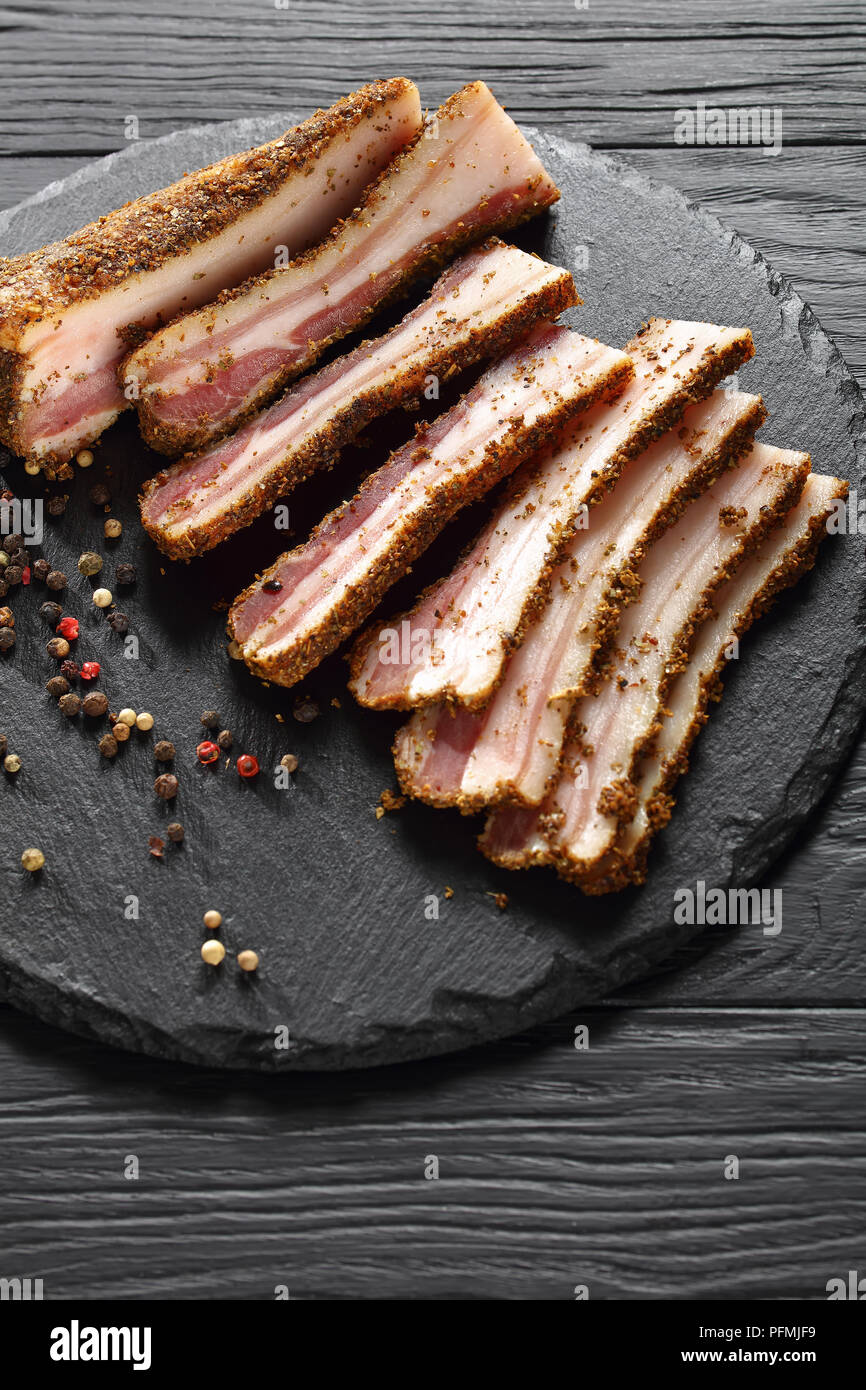delicious spicy smoked speck cut in slices on black round stone plate on wooden table,  vertical view from above Stock Photo