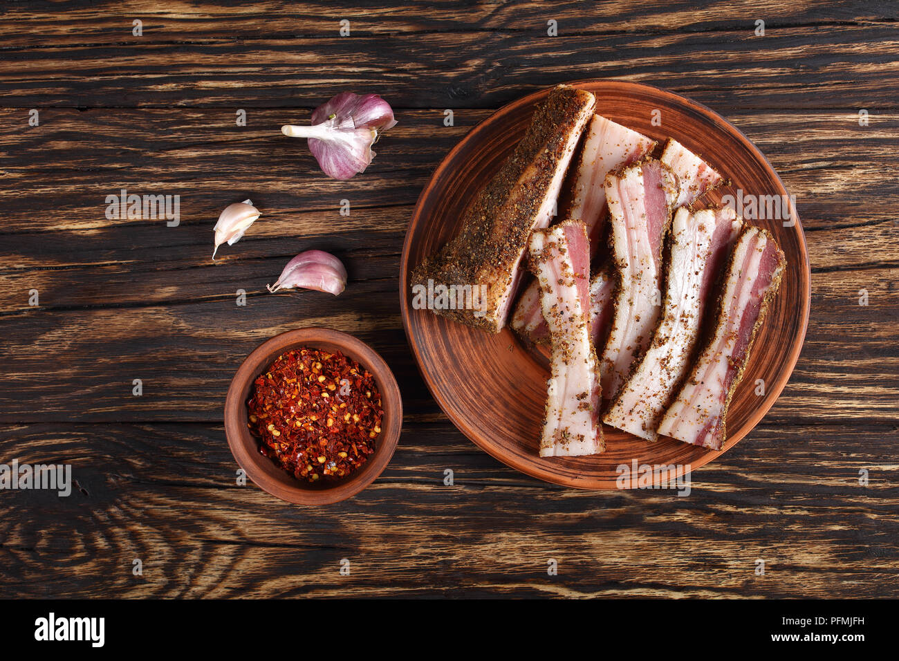 delicious sliced spicy air dried speck on clay plate on rustic wooden table with garlic  and chili flakes in bowl at background, horizontal view from  Stock Photo