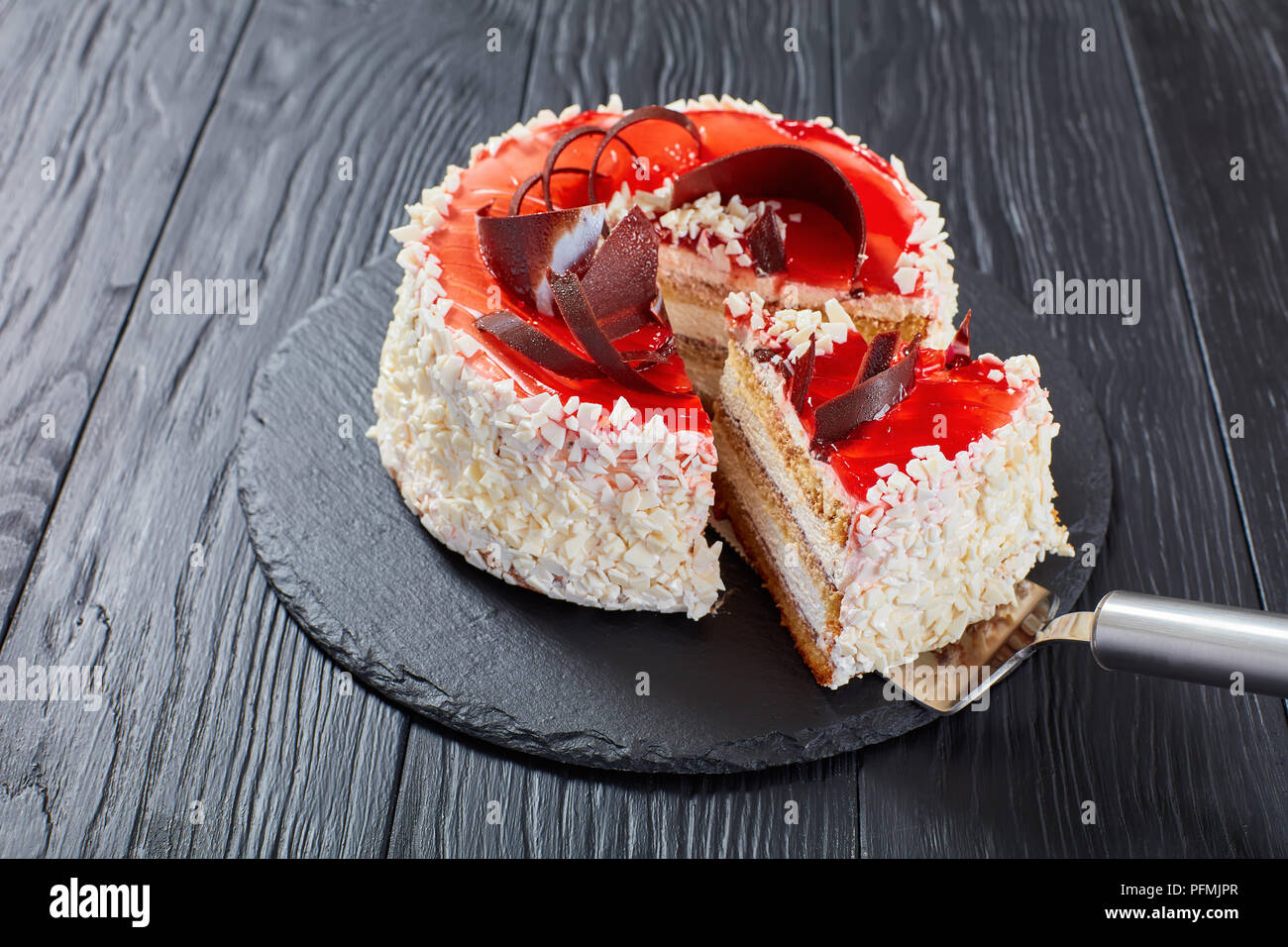 delicious sponge cake layered with cream cheese mousse decorated with white chocolate flakes, red berry jelly and chocolate chips on black slate plate - Stock Image