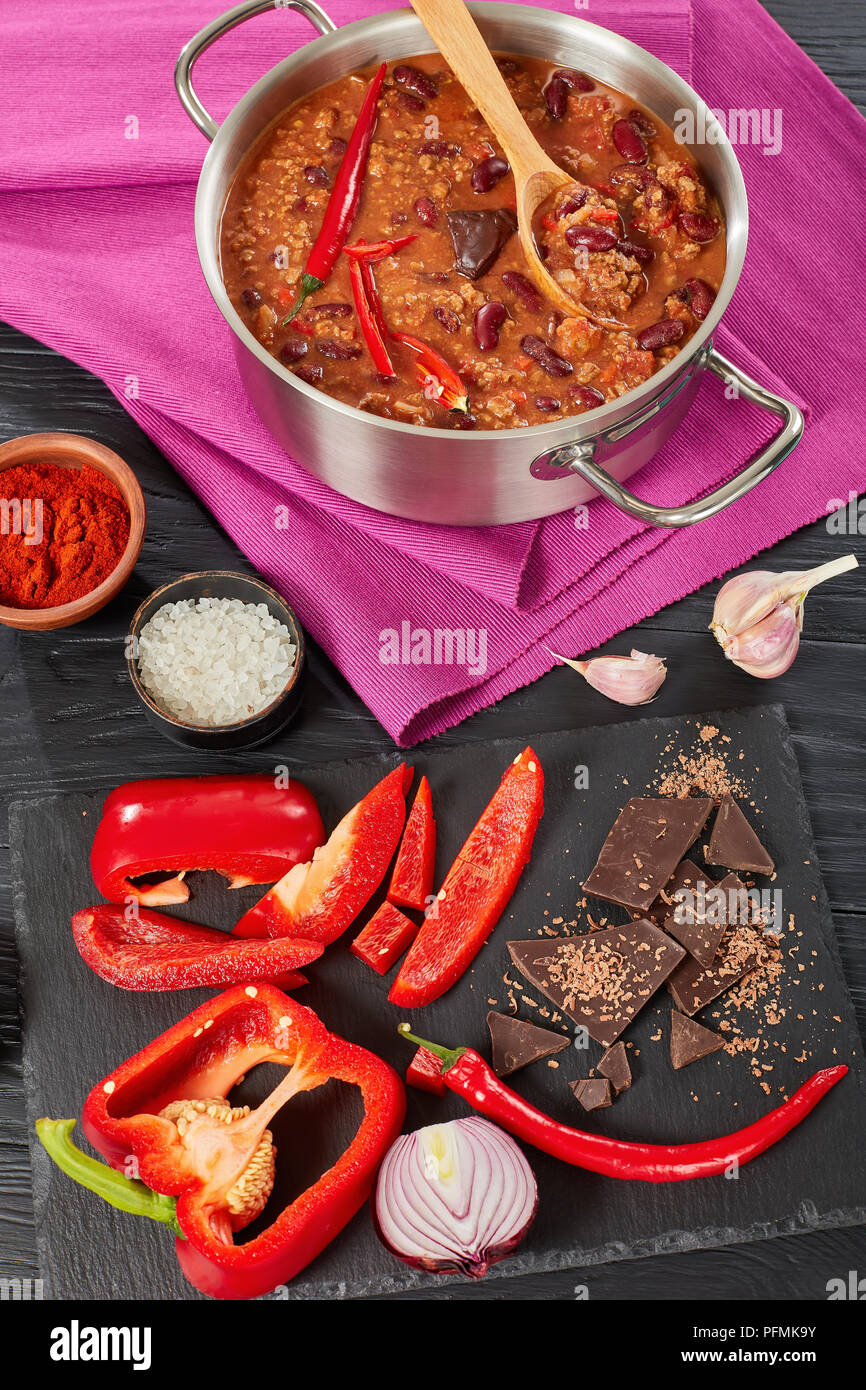hot delicious chili con carne with whole red hot chilis, kidney beans, tomatoes and piece of chocolate in a pot with ingredients at background, authen Stock Photo