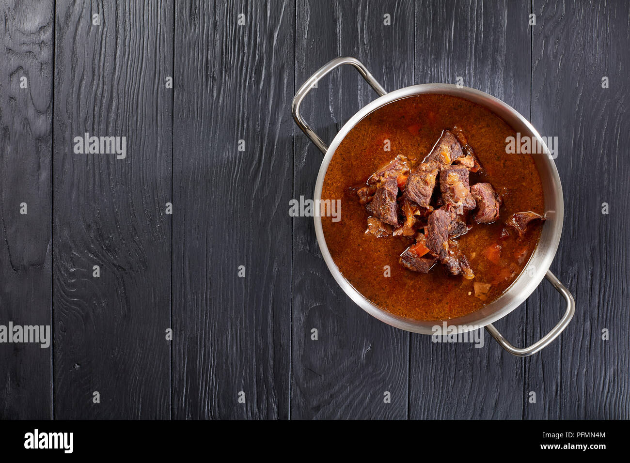 homemade hot Czech beef goulash in a stainless pan on black wooden table, view from above - Stock Image